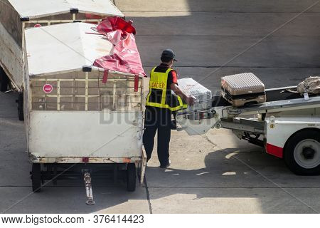 Asian Man Loader Lifting Up The Luggage To Conveyor Belt Of The Trailer To Loading Passenger Baggage