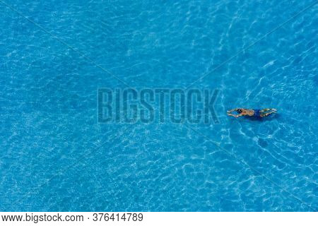 Top View Of Happy Man Is Relaxing And Enjoy Swimming In The Swimming Pool Of The Luxury Hotel And Re