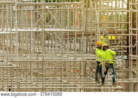 Asian Construction Workers Working On Scaffolding Of Building Construction Site In City. Urban Expan