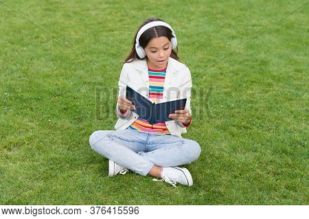 Development Of The Imagination. Cute Girl Read Book. Happy Preschool Girl With Book In School Yard.