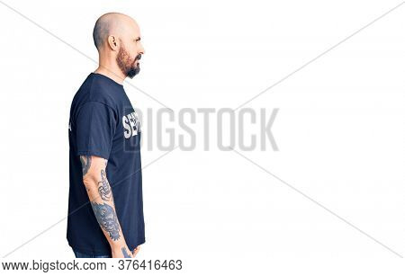 Young handsome man wearing security t shirt looking to side, relax profile pose with natural face and confident smile.