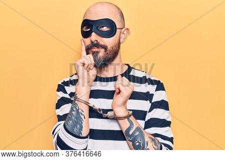 Young handsome man wearing burglar mask and handcuffs serious face thinking about question with hand on chin, thoughtful about confusing idea