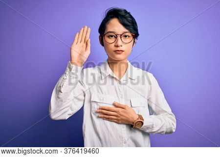 Young beautiful asian girl wearing casual shirt and glasses standing over purple background Swearing with hand on chest and open palm, making a loyalty promise oath