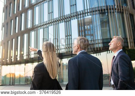 Businesspeople In Suits Pointing And Looking At Office Building, Discussing Real Property. Back View