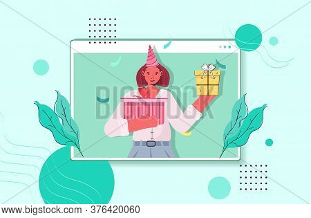 Woman In Festive Hat Celebrating Online Birthday Party Girl In Computer Window Holding Wrapped Gifts