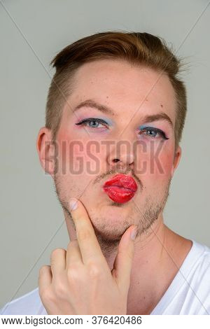 Portrait Of Young Man With Beard Stubble Wearing Makeup