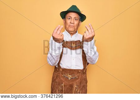 Senior grey-haired man wearing german traditional octoberfest suit over yellow background doing money gesture with hands, asking for salary payment, millionaire business