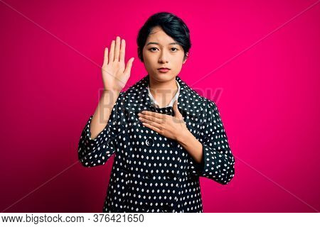 Young beautiful asian girl wearing casual jacket standing over isolated pink background Swearing with hand on chest and open palm, making a loyalty promise oath