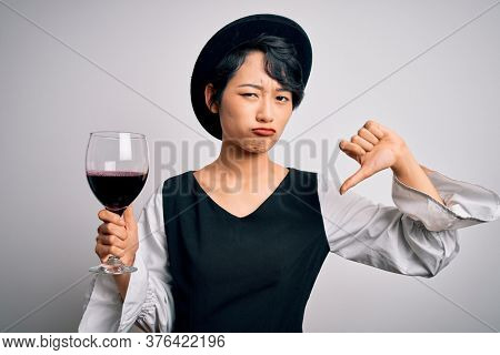 Young beautiful asian sommelier girl drinking glass of red wine over isolated white background with angry face, negative sign showing dislike with thumbs down, rejection concept