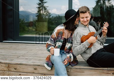 Happy Hipster Couple Relaxing On Wooden Porch Of Modern Cabin With Big Windows In Mountains. Hipster
