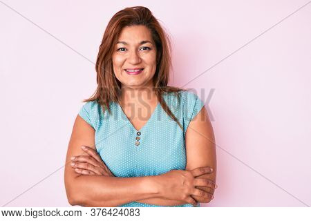 Middle age brunette hispanic woman wearing casual clothes happy face smiling with crossed arms looking at the camera. positive person.