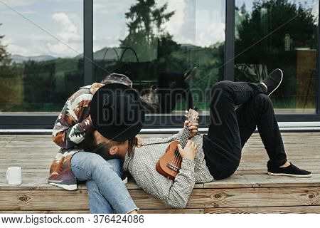 Hipster Man Playing On Ukulele For His Beautiful Stylish Woman, Relaxing On Wooden Porch On Backgrou