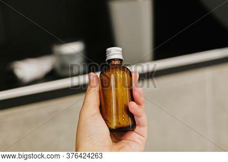 Hand Holding Ayurveda Ubtan Powder In Glass In Modern Bathroom On Background Of Stylish Black Shelf