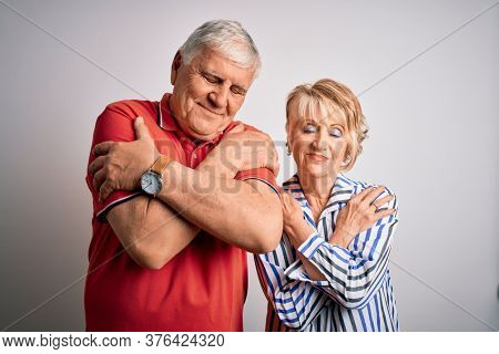Senior beautiful couple standing together over isolated white background Hugging oneself happy and positive, smiling confident. Self love and self care