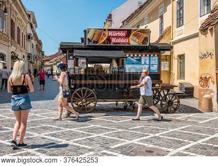 Brasov/romania - 06.28.2020: Walking Street In The Old Town Of Brasov. A Kurtos Kolacs Stand On Whee