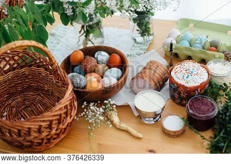 Easter Modern Eggs, Easter Bread, Ham, Beets, Butter, Green Branches  And Flowers On Rustic Wooden T