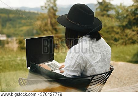 Hipster Girl With Laptop Sitting On Wooden Porch With Beautiful View On Woods And Mountains. Stylish