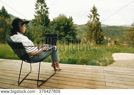 Stylish Hipster Girl Sitting With Laptop On Terrace With View On Woods. Young Happy Woman In Hat Usi