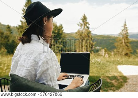 Freelance. Hipster Girl With Laptop Sitting On Wooden Porch With Beautiful View On Woods And Mountai