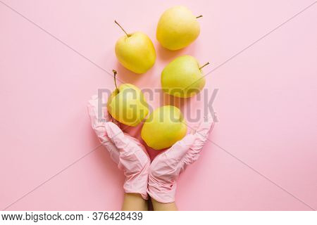 Hands In Pink Glove Holding Apples On Pink Background Flat Lay. Order Groceries And Get Them Deliver
