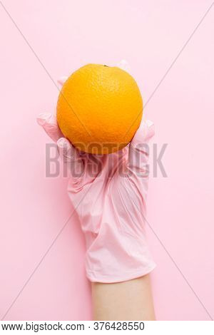 Hand In Pink Glove Holding Orange On Pink Background Flat Lay. Safe Shopping In Quarantine. Order Fo