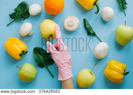 Hand In Pink Glove Picking Groceries On Blue Background With Vegetables Flat Lay. Order Fresh Organi