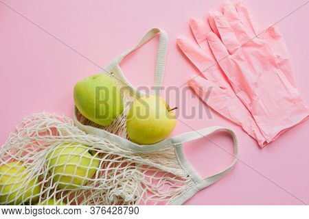 Safe Shopping In Quarantine Concept. Pink Gloves And Tote Bag With Fresh Apples On Pink Background F