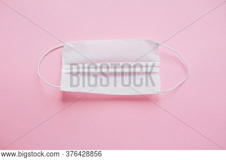 Face Mask On Pink Background Flat Lay. Coronavirus Pandemic. Stay Safe. Prevention Of Virus Epidemic