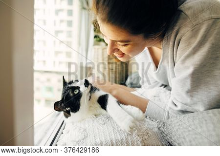Young Woman Playing With Cute Cat, Sitting Together At Home During Coronavirus Quarantine. Stay Home