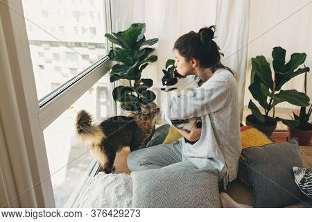Hipster Girl Hugging And Playing With Two Cats In Modern Room, Sitting Together At Home During Coron
