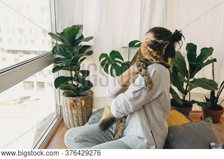 Hipster Girl Playing With Cute Cat, Sitting Together At Home During Coronavirus Quarantine. Stay Hom