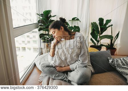 Sad Hipster Girl Holding Pillow, Sitting At Home During Quarantine. Isolation At Home To Prevent Vir