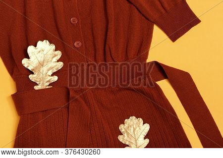 Fashion Terracotta Knitted Dress, Golden Autumn Leaves On Yellow Paper Background With Copy Space. L