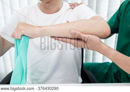 Male Physiotherapists Provide Assistance To Male Patients With Elbow Injuries To Examine Patients In