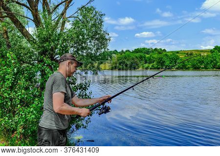 Young Adult Fisherman Casts A Fishing Rod Into The River. Portrait Of A Man Fishing On A Background