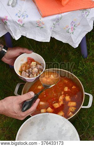 Cast-iron Cauldron With Soup At The Stake In The Courtyard. Summer Day And Dinner In The Fresh Air N