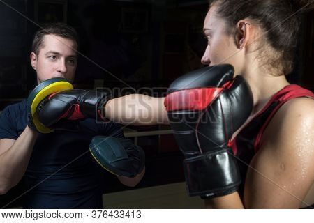 Portrait Of A Boxing Trainer Guy Training A Young Athlete Training Her In Martial Arts. In A Boxing