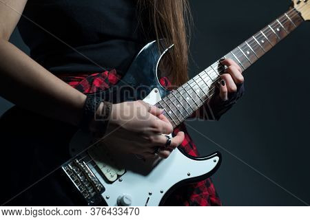 Close-up Female Hands Play Hard Rock And Roll Rhythmic Figure. Studio Photo On A Gray Background. Di