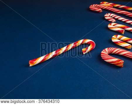 Christmas Candy Cane. On Classic Blue Background. Flat Lay. Christmas Composition. A Fan Of Caramel