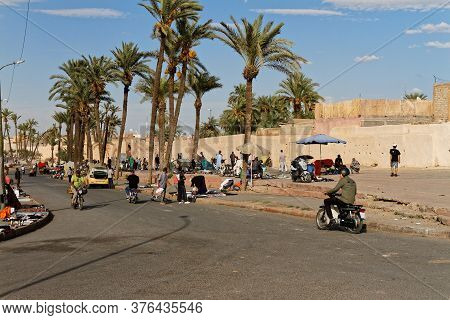 Marrakech, Marocco Okt, 7, 2018, Street Market On Sidewalk, Blue Sky With Old City Wall And Palm Tre