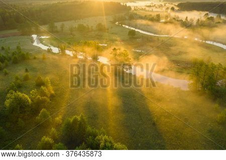 Summer Misty Morning On Meadow. Morning Sun Rays Over Valley With River. Sunny Scenic Rural Backgrou