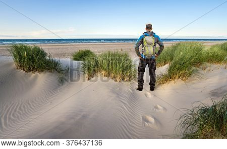 Man With Backpack Hiking In Beautiful Windy Coastal Dune Marram Grass Towards Beach Of North Sea In