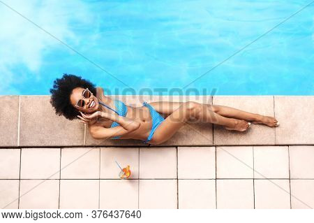 Overhead View Of Sensual Black Girl With Refreshing Cocktail Resting At Poolside, Copy Space