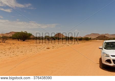 African Desert Dirt Road With Partial White Car In Hot Red Kalahari Sand Landscape With Small Trees