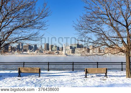 A view across the St Lawrence river to downtown Montreal. Winter shot with snow on the ground and mist rising from the frozen water. Cityscape framed by bare trees with two benches in the foreground.