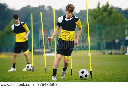 Soccer Education; Training With Agility Poles. Youth Soccer Players On A Drill. Football Training Fo