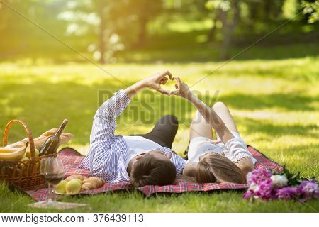 Loving Couple Making Heart With Hands During Picnic At Park In Summertime