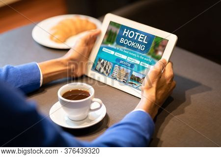 Unrecognizable Black Man Booking Hotel On Tablet Computer Sitting In Cafe Indoors. Searching Travel