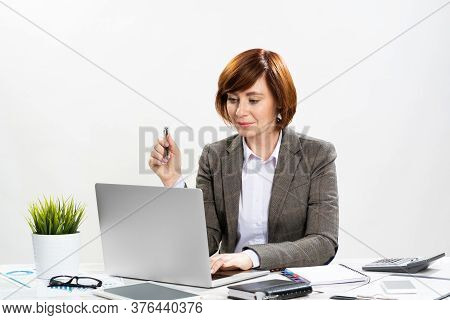 Attractive Middle Aged Businesswoman Working With Computer In Office. Concentrated Business Lady Sit
