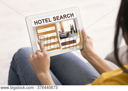 Unrecognizable Woman Booking Hotel Room Using Digital Tablet Sitting At Home. Travel Accommodation S